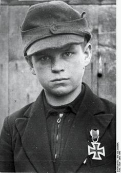 12-year-old Hitler Youth member Alfred Zech from Goldenau, Germany, posing with his Iron Cross 2nd Class medal, March 1945