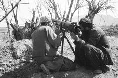 Two Afghan fighters line up an 82mm recoiless rifle before firing at a Soviet security post along the main highway west of Kandahar on March 21, 1985.