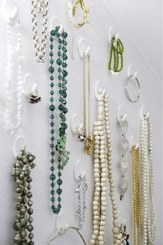 """This is probably the most compatible necklace storage method for my plaster walls--sticky hooks.  It displays them so they're all visible but doesn't put a thousand holes in the wall--a wall that doesn't really """"give"""" to even one nail.  lol"""