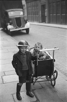 A boy in London wears a steel helmet for protection during The Blitz, 1940.