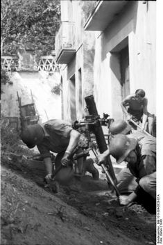 Italy, 1943: German troops fire a mortar from inside the yard of a house. Undisclosed location. The Germans put up a stiff fight in Italy in the effort to frustrate the Allied effort to attack Germany from the south.