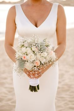 Blush wedding bouquet with roses, baby's breath and greenery | Beachfront destination wedding at Riu Palace Cabo San Lucas in Los Cabos, Mexico | Fostered Photo