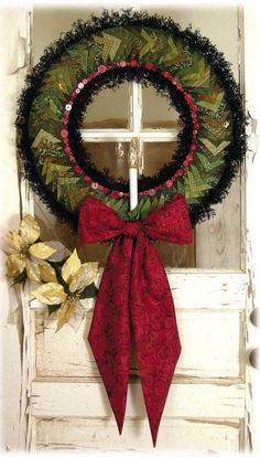"Pattern name: PINWHEEL HOLLY WREATH ~ ""Impress your friends with this beautiful wreath. Super simple construction using one block and simple step and repeat. Prairie points create an irresistible dimensional look. Features Ozsome Accents cordless candle ( batteries not included ). Finished size 24""."" ~ Great Christmas decor!"