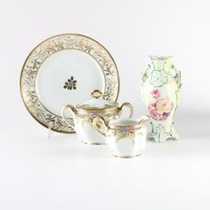 A collection of hand-painted Nippon porcelain and a hand-painted vase from Austria. This collection includes four pieces. Offered is a hand-painted Nippon serving dish with a foliate motif in gilt, a Nippon creamer and sugar, and a vase made in Austria. The cream and sugar have gilt trim. The accompanying vase has a floral motif against a pastel background. The pieces are marked to the bottom.