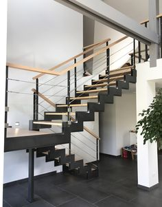 Escalier intérieur demi tour avec palier intermédiaire. Cet escalier à double limons crémaillère découpés est composé de marches en bois, sans contre marche. Son garde-corps est composé de poteaux en fer plats, de câbles en inox et d'une main courante ronde en bois. Un système d'éclairage à leds est installé dans le double limon.  #staircase #stairway #stairs #escalier #interiordesign #design #architecture #madeinfrance
