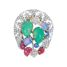 Gold, Platinum, Sapphire, Carved Emerald and Ruby and Diamond Clip-Brooch, Seaman Schepps Centering 2 pear-shaped carved emerald leaves, 2 oval sapphires approximately 5.75 cts., 2 round cabochon rubies and 4 carved rubies, accented by diamond-set leaves, within a delicate platinum openwork horseshoe-shaped frame decorated with diamond-set flowers, signed Seaman Schepps, one diamond missing, approximately 18 dwt.