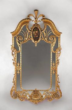 "We would like to present an exceptional 19th century English carved giltwood margin-glass wall mirror with a scrolled Rococo frame topped by the most beautiful ""Prince of Wales"" feather cresting we've ever seen. The mirror is further decorated with egg and dart molding, scrolled pierced work, and a hand painted floral pillar-medallion, which enhances the gold leaf finish to perfection."