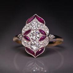 Antique Early Art Deco Diamond Ruby Engagement Ring, Austrian, Vienna, circa 1915. A delicate early Art Deco platinum topped 14K gold engagement ring is densely set with bright white old European cut diamonds accented by stylized ruby leaves. #AntiqueJewelry