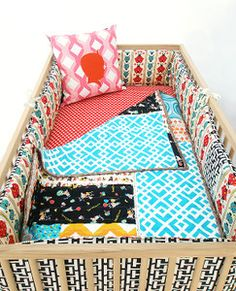 Reversible crib bumper set in 100% cotton with turquoise & ruby red ladybugs retro style wallpaper design on one side and 100% cotton twill with black and off white retro style graphic.