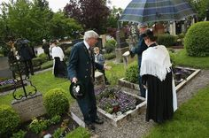 Participants wearing traditional Bavarian folk costumes visit the local cemetery under drizzling rain after attending the annual Corpus Christi (Fronleichnam in German) mass at St. Michaels Church in Seehausen am Staffelsee, Germany, on May 30, 2013. The Seehausen Corpus Christi celebration usually includes a procession to a chapel across the nearby Staffelsee lake, though rain forced organizers to cancel the lake procession this year.