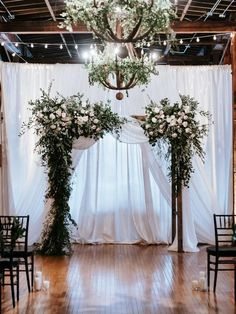 This stunning floral arch for the ceremony brought the garden-inspired decor indoors in this lush Industrial wedding in Tennessee. Lots of greenery and white and blush roses, garden roses, astilbe, ginestra and spray roses adorned this arbor fit for a Fai