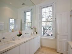 Plantation shutters provide a stylish window treatment in this double-vanity bathroom that can be easily closed for privacy or left open for natural light.