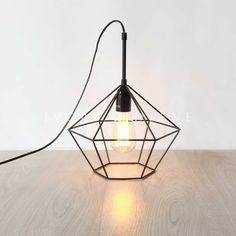 black diamond cage pendant sitting on a wooden floor with the light on