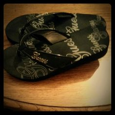 Guess Platform Flip Flops All black platform sandals size size. Platform itself is 1 1/2 inches, just a little lift. Guess logo written all over shoes ( even the bottom as shown in the last picture.) The straps have a Guess emblem with a sparkling black background on both shoes. Guess Shoes Platforms