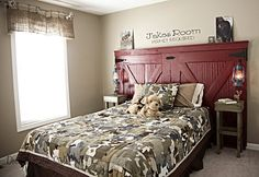 a barn door becomes a headboard - how cool! By Down to Earth Style Look at the camo quilt !
