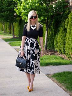 Splatter-print black and white skirt, black top, white statement necklace, heels with a pop of color