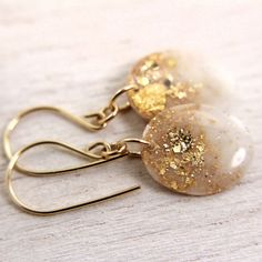 white earrings with gold glitter and gold leaf on by tinygalaxies, $24.00