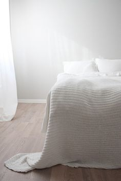 Plain white sheets and curtain. Solid wood floors. Texture blanket. Simple.