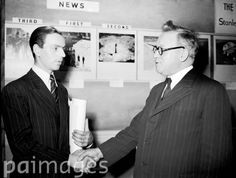 Roy Illingworth, a PA-Reuter photographer (left) receives congratulations from Herbert Morrison MP, after he won a photographic competition with one of his sports photographs.