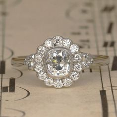 $4800   This stunning Art Deco style Diamond engagement ring features a central Old Cushion Cut Diamond dating from the 1920's. The Diamond is bezel set