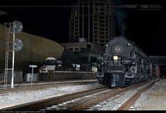 "As Norfolk and Western ""A"" class #1218 simmers behind the O. Winston Link Museum in Roanoke, VA, NS SD70M-2 #2765 rolls by with train #18M, a daily freight operating between Elkhart, Indiana, and Linwood, North Carolina."