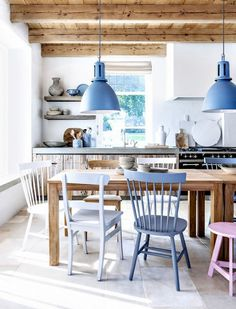 In this otherwise-neutral Scandinavian kitchen, a clever paint job blends shades of pinks and blues around the dinner table. Chairs and pendants are each painted in their individual shade.