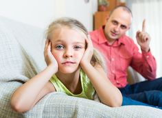 Serious father 30s rebuking small daughter for offence at home