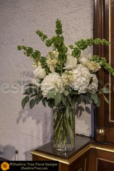Clear glass vases held white, green and cream flowers including hydrangea, roses, stock, and bells of Ireland !