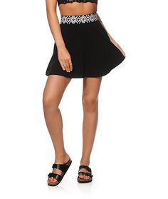 A thick elastic waistband with woven tribal detailing accents the solid colored skirt cut with a flattering skater silhouette for an on-trend look.