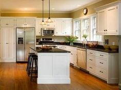 White shaker cabinets, overhead cabinets with crown moulding, island bench end detail and skirting