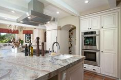 A double oven is built into the cabinetry in this French country-inspired kitchen, allowing meal preparation for a crowd. Across from the double oven, a prep sink and cooktop are incorporated into the peninsula for the chef's convenience.