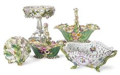 A GERMAN PORCELAIN TWO-HANDLED BASKET AND A GROUP OF ENGLISH FLOWER-ENCRUSTED WARES,<br />THE FIRST MEISSEN (MARCOLINI), BLUE CROSSED SWORDS MARK, 18TH CENTURY, THE ENGLISH WARES, 19TH CENTURY,<br />the flower encrusted wares comprising a pair of Coalbrookdale green-ground baskets, with blue marks; two hydrangea-form vases; and a pair of reticulated compotes<br />The pair of baskets 8¾in. (22.2cm.) long (7)<br />