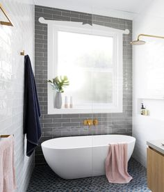 Stand alone tub inside walk in shower with grey tiled statement wall | GIA Renovations