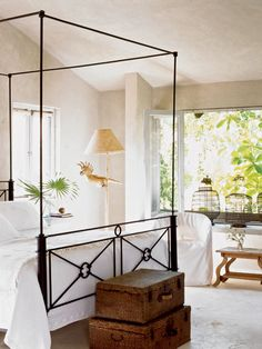 """When decorating this Mexican hideaway, designer Myra Hoefer wanted the house to look like it had been abandoned years ago, and the sand and sea had swept over it. All of the items in the house would have been washed up from a shipwreck on the beach. """"Spanish settlers would have brought these beds over with them,"""" Hoefer says of this iron four-poster bed with an almost colonial look to it. (Photo: Lisa Romerin)"""