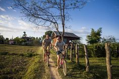 Backpackers exploring Don Det by bicycle, Laos - Matthew Micah Wright/Getty Images
