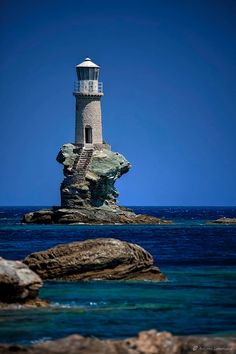Tourlitis Lighthouse, Andros Island, Greece. Greek islands 1887. Active;(62 ft); two white lights flashes every 15 sec. stone tower perched on an isolated rock stairs cut into the rock lead down to a crude landing site Ándros Chóra is a frequent stop for cruise ships,Located on a rock in the harbor of Ándros Chóra. Accessible only by boat.
