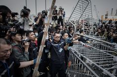 Umbrella Revolution Hong Kong, Security staff members remove a barricade outside the CITIC Tower building near a pro-democracy protest site in the Admiralty district of Hong Kong on November 18, 2014. Security staff members assisted by Hong Kong bailiffs took action at pro-democracy barricades outside the building located near the main protest sites in the city, as pressure grows on demonstrators to leave. AFP PHOTO / Philippe Lopez (Photo credit should read PHILIPPE LOPEZ/AFP/Getty Images)