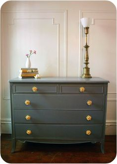 Dark gray painted dresser as a TV stand... minus the flower knobs.