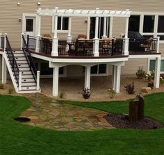Backyard deck with patio at the base of stairs. Techdeck decking in dark-brown and bright white pergola over part of the deck.   houzz.com