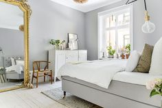 Bedroom with light grey walls and a large golden mirror