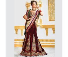 The maroon color velvet based Lehenga saree. Blouse portion of the saree has thick embroidery of traditional design. The skirt portion has embroidered patch work stitched vertically. The border of the saree has embroidered border with stone stud design. The pallu portion has thick velvet embroidered patch borders. The saree is perfect for parties and occasional events.
