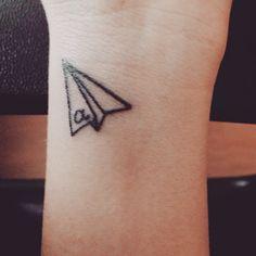 Little wrist tattoo of a paper plane