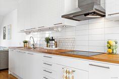 Stilrent och snyggt kök från Ballingslöv med vita luckor ända upp till tak. Bänkskiva i ek och vitt kakel.