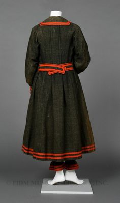 Woman's bathing ensemble  c. 1875 Dark wool bathing costumes were often styled to resemble nautical uniforms, with red or white braided trim and sailor collars. Some early bathing costumes were made of silk, which tended to leach its dye onto the wearer when wet. Both wool and silk clung to the skin when wet, so many bathers had a coordinating cape or wrap which was worn over the wet bathing costume.