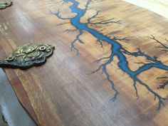"""Live edge Pear wood clothes hanger with glow in the dark Lichtenberg figure blue resin inlay and ancient bronze hooks. """"Sunrise"""" by ValentinoBanini on Etsy"""
