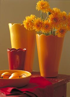 Hand glazed pottery in oranges and red with a red farm table.