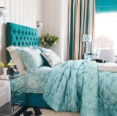 #Bedroom with teal tufted #headboard with mirrored nightstand and quilted duvet
