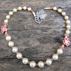 This pretty glass pearl necklace features creamy ivory pearls in three sizes along with pink glass spacers and dark pink (almost red) polymer clay lilies. The clasp is a gorgeous antique silver grape leaf toggle and the necklace, itself, is approximately Pearl Necklace, Beaded Necklace, Ivory Pearl, Antique Silver, Polymer Clay, Lily, Jewelry Making, Pearls, Antiques