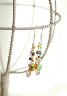 impress me earrings  $12.99  Sparkling beads in purple, green, and amber shimmer from these gold tone drop earrings.