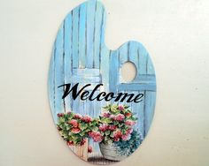 Rustic, paint palette shaped, wood sign with Welcome text on an old blue door with potted flowers. Welcome your guests with a beautiful rustic sign. You can put it on your door, wall or every corner of your house. Perfect gift for your friends, mom, grandmother, who loves
